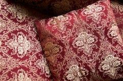 Lyxiga kuddar på säng i guld- brokad Royaltyfri Fotografi