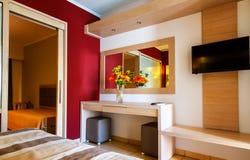 Lyxiga moderna hotellruminredetaljer spegel och vas av blommor på tabellen royaltyfri foto