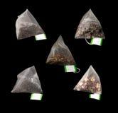 5 lyxiga pyramidTeabags som isoleras på svart Arkivfoton