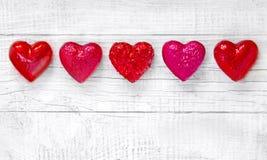 Lyxiga röda hjärtor på vit träbakgrund lyckliga valentiner för dag Blänka förälskelsekonfettier Royaltyfria Bilder