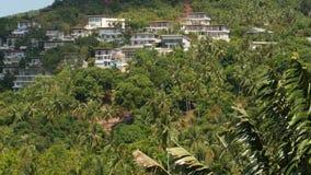 Lyxiga villor på berglutning Surrsikt av lyxiga hus som lokaliseras under exotiska träd på det gröna berget på solig dag lager videofilmer