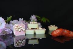 Lyxiga vita choklader på den svarta glass tabellen Royaltyfria Foton