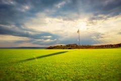 Lyxigt fält i en golfklubbkurs på solnedgången Arkivfoto