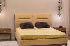 Lyxigt guld- färgsovrum i modern stil med den rika dekoren och sängkantlampor royaltyfri bild