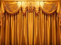 Lyxigt guld- tyg hänger upp gardiner bakgrunden på theaten Royaltyfri Fotografi