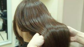 Lyxigt hår i händer av frisören arkivfilmer