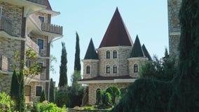 Lyxigt hotell i viktoriansk stil som f?rdjupas i h?rliga tr?d och buskar tak med spiers p? en bakgrund av klart arkivfilmer