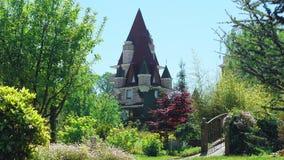 Lyxigt hotell i viktoriansk stil som f?rdjupas i h?rliga tr?d och buskar tak med spiers p? en bakgrund av klart arkivbilder