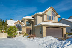 Lyxigt hus för familj med den främre gården i snö Arkivbild