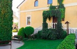 Lyxigt hus med den utmärkt klippte och landskap främre gården Arkivbilder