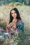 Lyxigt indiskt kvinnasammanträde i fält blommar på naturligt, dre royaltyfri foto