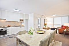 Lyxigt kök med den vita äta middag tabellen och soffan royaltyfri fotografi
