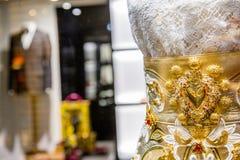Lyxigt lager med den eleganta guld- klänningen och dräkt på bakgrund Royaltyfri Bild