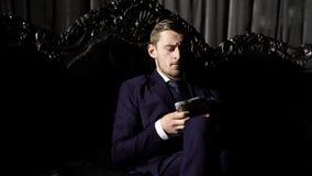Lyxigt livbegrepp Mannen i dr?kt, aff?rsman sitter i m?rk lyxig inre bakgrund Lyxig rik livsstil lager videofilmer