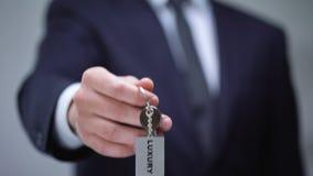 Lyxigt ord på keychain i den manliga handen, storgubbehotellrum för affärsklientcloseup stock video