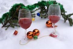 Lyxigt rött vin i sörjer i en härlig vit snöig julplats arkivbilder