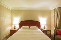 Lyxigt rymligt sovrum med sidotabelllampor och bekväm stol Royaltyfri Fotografi