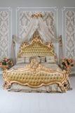 Lyxigt sovrum i ljusa färger med guld- möblemangdetaljer Stor bekväm dubbel kunglig säng i elegant klassiker royaltyfri foto