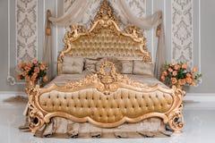 Lyxigt sovrum i ljusa färger med guld- möblemangdetaljer Stor bekväm dubbel kunglig säng i elegant klassiker arkivfoto