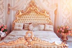 Lyxigt sovrum i ljusa färger med guld- möblemangdetaljer Stor bekväm dubbel kunglig säng i elegant klassiker royaltyfri fotografi