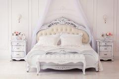 Lyxigt sovrum i ljusa färger med guld- möblemangdetaljer Stor bekväm dubbel kunglig säng i elegant klassiker arkivbilder