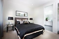 Lyxigt sovrum inklusive svarta duntäcke och toalettingången royaltyfri bild