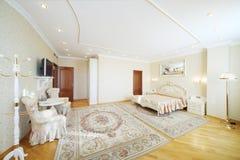 Lyxigt sovrum med härlig dubbelsäng, med fåtöljer arkivfoto