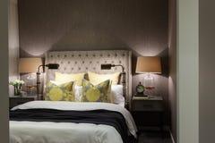 Lyxigt sovrum som är upplyst på natten med closeupen för tabelllampor arkivbild