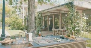 Lyxigt utomhus- kök i en stor trädgård