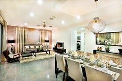 Lyxigt vardagsrum- och äta middagområde med hängande ljus Fotografering för Bildbyråer