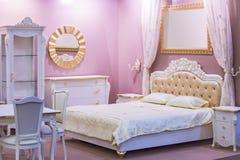 Lyxigt vit- och rosa färgsovrum i antik stil med den rika dekoren Inre av ett klassiskt stilsovrum i lyxig lägenhet fotografering för bildbyråer