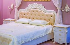Lyxigt vit- och rosa färgsovrum i antik stil med den rika dekoren Inre av ett klassiskt stilsovrum i lyxig lägenhet royaltyfri bild