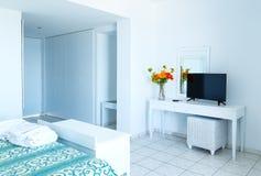 Lyxigt vitt sovrum med TV och mirrow i lägenheten arkivfoto