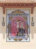 MÀLAGA, SPANIEN - 25. MAI 2015: Keramische mit Ziegeln gedeckte, geschrieene Madonna unter der Kreuzigung auf der Fassade der Kir Lizenzfreies Stockfoto
