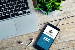 MÀLAGA, SPANIEN - 29. OKTOBER 2015: Wordpress-Anmeldungs-Website-APP auf einem Handyschirm, über einem hölzernen Arbeitsplatz Wor Lizenzfreie Stockfotografie