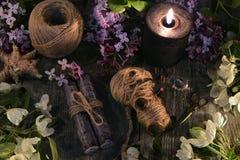 A mágica do vudu com boneca, velas pretas, objetos místicos e mola floresce foto de stock royalty free