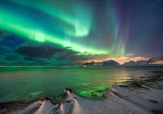 Mágica real da aurora boreal - fiorde norueguês com neve e montanhas imagens de stock royalty free