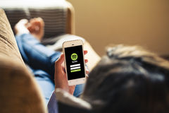 MÁLAGA, ESPAÑA - 26 DE ABRIL DE 2015: Spotify App en un control móvil de la pantalla de la mujer mientras que miente de un sofá e Fotografía de archivo libre de regalías
