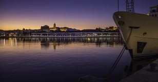 Málaga port sunset. Photography of a sunset in Málaga port with view of Palmeral de las Sorpresas promenade and city center and detail of a boat in front Stock Photo