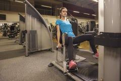 Máquina abductora del uso apto de la mujer de los jóvenes en un centro de aptitud Retrato de la muchacha en el gimnasio, concepto Foto de archivo libre de regalías