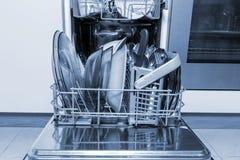 Máquina aberta da máquina de lavar louça com pratos e a cutelaria limpos, utensílios de mesa, azul tonificado fotografia de stock royalty free