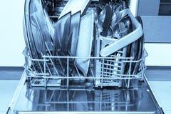 Máquina aberta da máquina de lavar louça com pratos e a cutelaria limpos, utensílios de mesa, azul tonificado fotografia de stock
