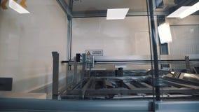 A máquina automática imerge as lentes que penduram na haste de metal em agitar o quadro video estoque