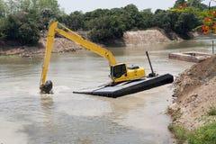 A máquina da máquina escavadora funciona no rio Imagem de Stock Royalty Free