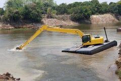 A máquina da máquina escavadora funciona no rio Fotografia de Stock Royalty Free