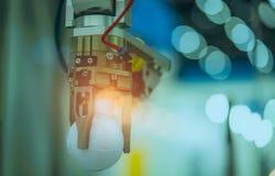 A máquina da mão do robô que pegara a bola branca no bokeh borrou o fundo Use o robô esperto na indústria de transformação para a imagens de stock