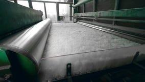 A máquina da planta rola o material branco do poliéster, movendo sobre uma linha filme