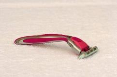 Máquina de afeitar de la señora rosada en una toalla Foto de archivo