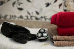 Máquina de afeitar rotatoria azul eléctrica con tres cuchillas cerca de la caja y de las toallas de baño negras imágenes de archivo libres de regalías