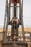 Máquina de bombeamento do óleo em um campo desencapado de Brown Imagens de Stock Royalty Free